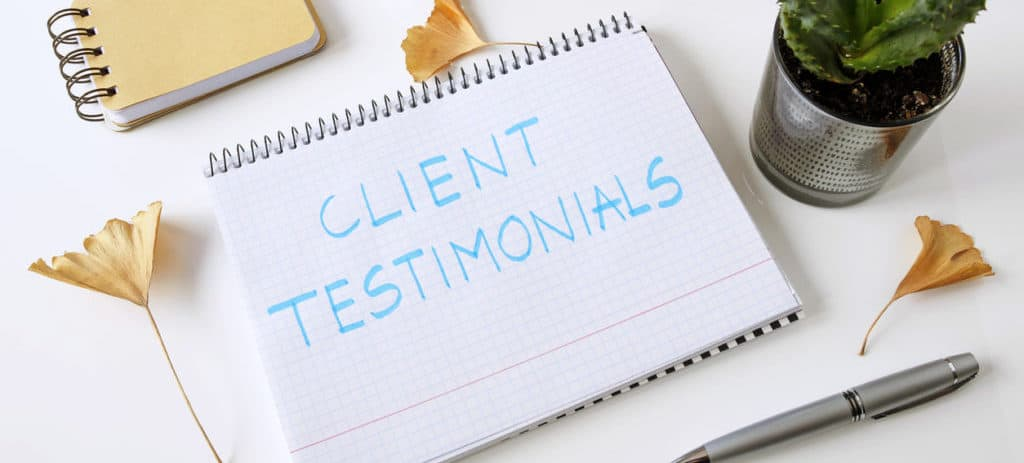 client testimonials written in a notebook on white table